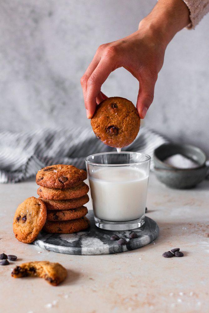 Cookies Choco Chips com mão a molhar no leite